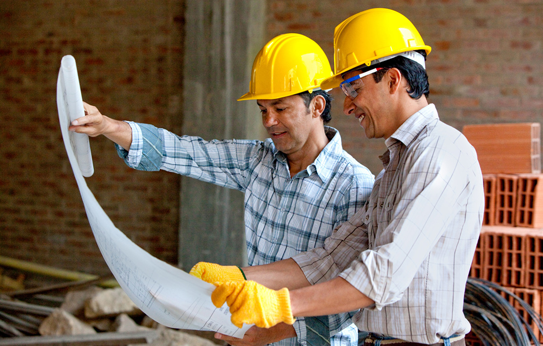 Two artisan contractors wearing hard hats reviewing plans