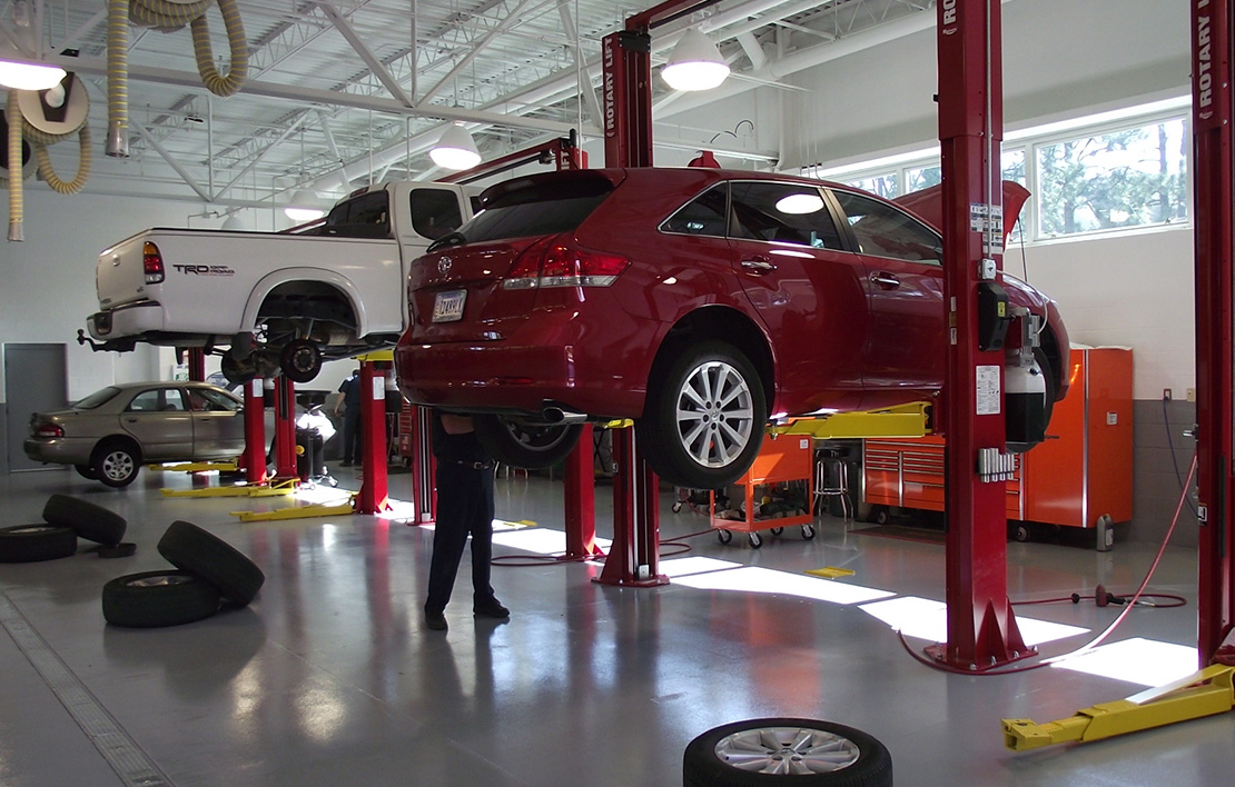 Red car and white truck on lifts at an auto repair shop