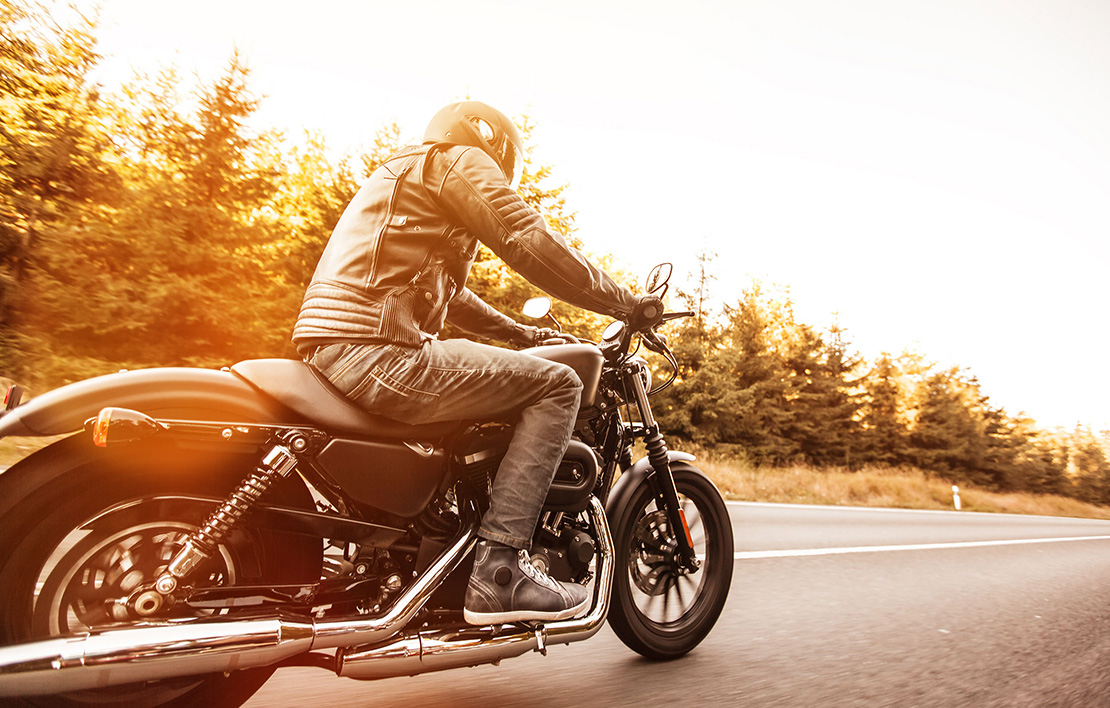 Male riding motorcycle on open road