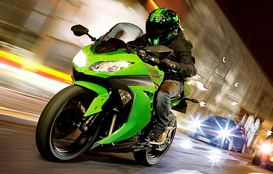 Male riding a green and black ninja bike