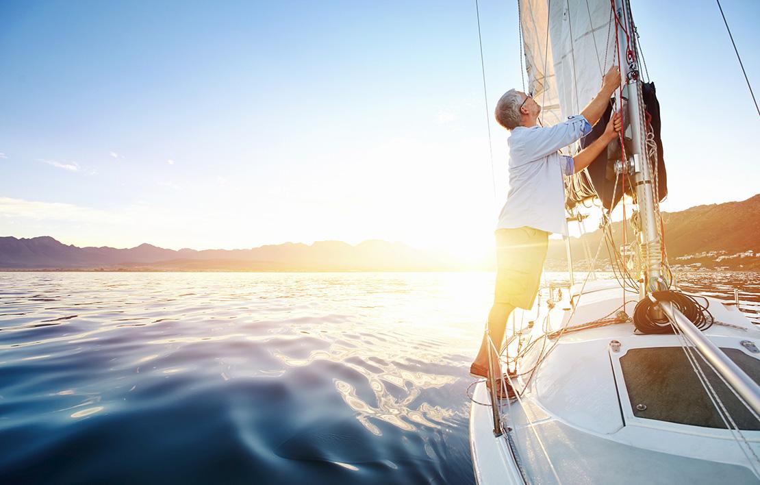 Man on sailboat raising sail boat insurance - boat 2x - Boat Insurance