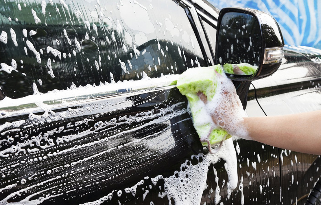 Person hand washing a black car with a yellow sponge
