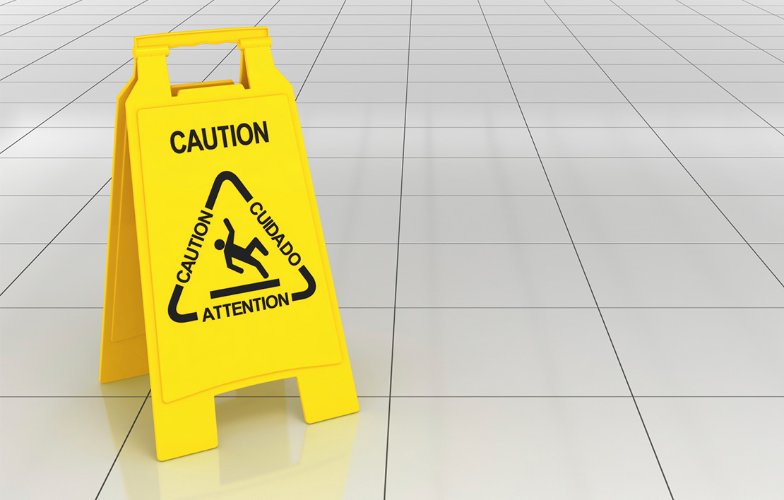 Caution sign on a white tiled floor