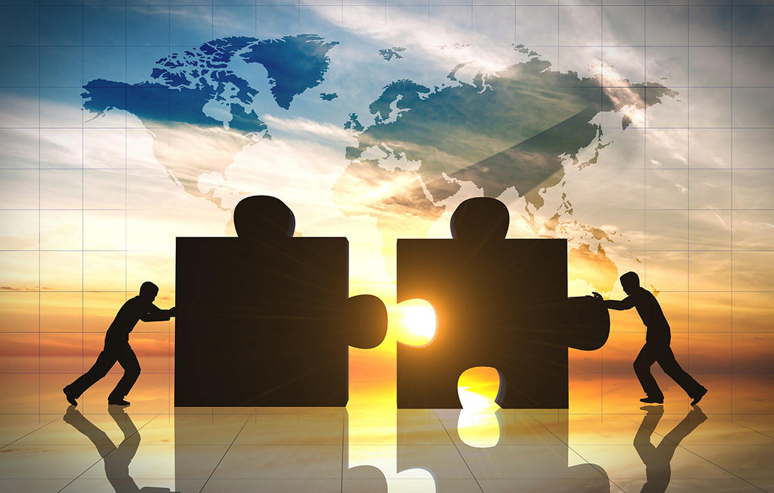 Two males pushing together puzzle pieces as the sun sets acquisitions - acquisitions 2x - Acquisitions