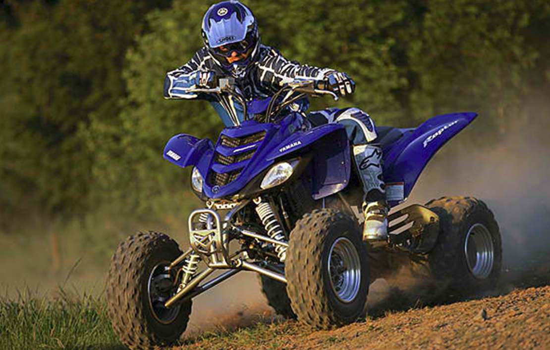 Male riding blue Yamaha ATV