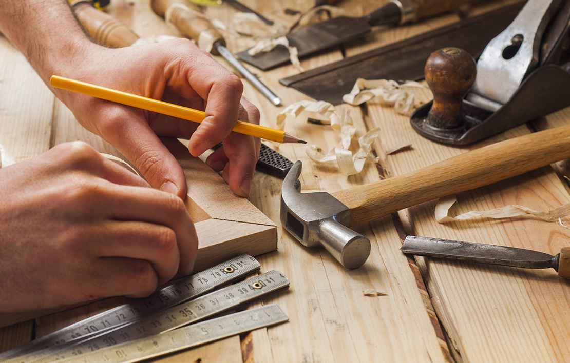 A carpenter surrounded by tools, putting together two pieces of angles wood on a work bench