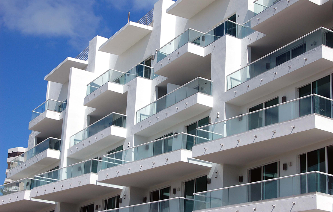 Picture of a white condominiums with glass porch enclosures