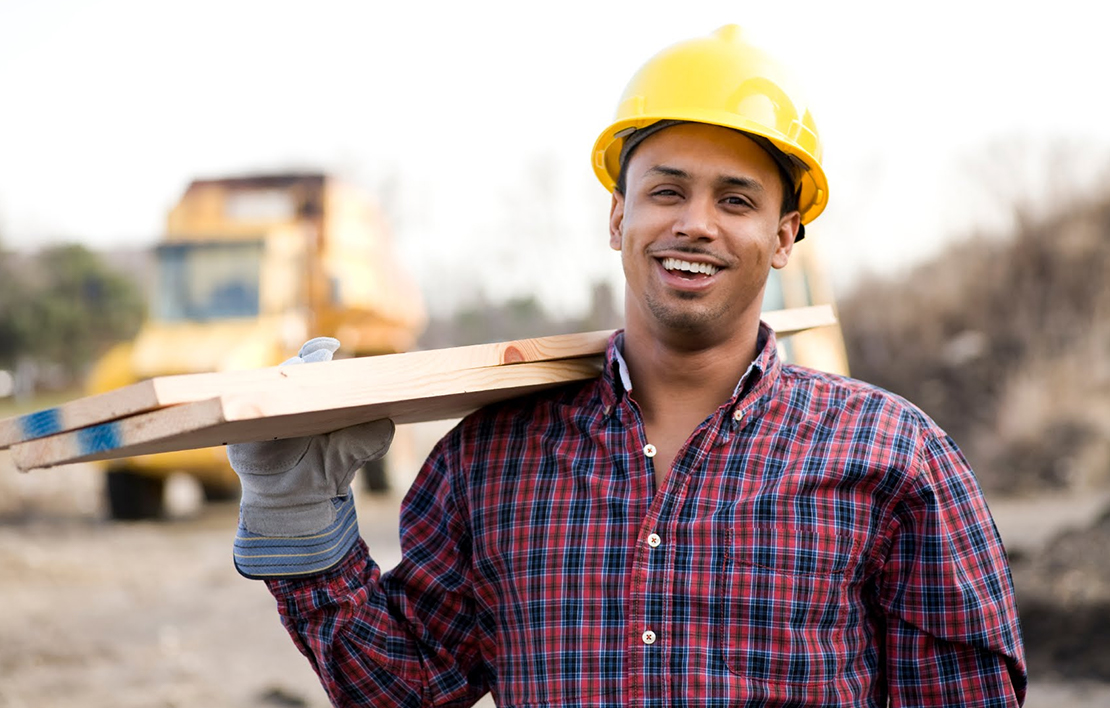 A male contractor in a hard hat carrying two pieces of wood