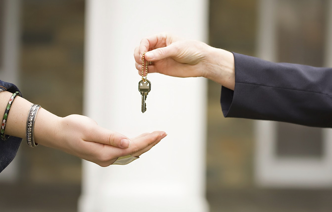 Picture of a woman handing a key to another woman landlord - landlord 2x - Landlord